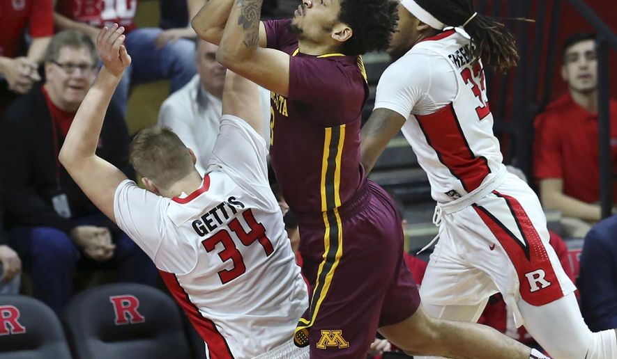 Minnesota forward Jordan Murphy, center, shoots as he splits Rutgers defenders center C.J. Gettys, left, and forward Deshawn Freeman, right, during the first half of an NCAA college basketball game, Saturday, Feb. 11, 2017, in Piscataway, N.J. (AP Photo/Mel Evans)