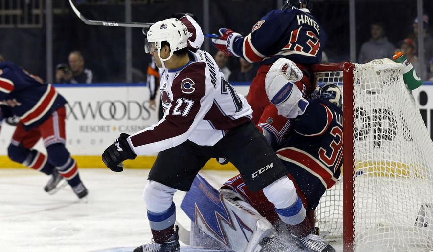 Colorado Avalanche left wing Andreas Martinsen (27) checks New York Rangers center Kevin Hayes (13) into Rangers goalie Henrik Lundqvist during the first period of an NHL hockey game Saturday, Feb. 11, 2017, in New York. (AP Photo/Adam Hunger)