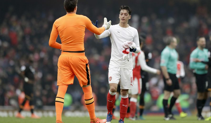 Arsenal's Mesut Ozil, right, swaps shirts with Hull City's goalkeeper Eldin Jakupovic after the final whistle of the English Premier League soccer match between Arsenal and Hull City at the Emirates Stadium in London, Saturday, Feb. 11, 2017. (AP Photo/Matt Dunham)