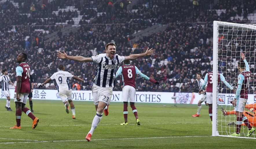 West Bromwich Albion's Gareth McCauley, center, celebrates their last minute equaliser goal during the English Premier League soccer match between West Ham United and West Bromwich Albion at London Stadium, Saturday, Feb. 11, 2017.  (Scott Heavey/PA via AP)