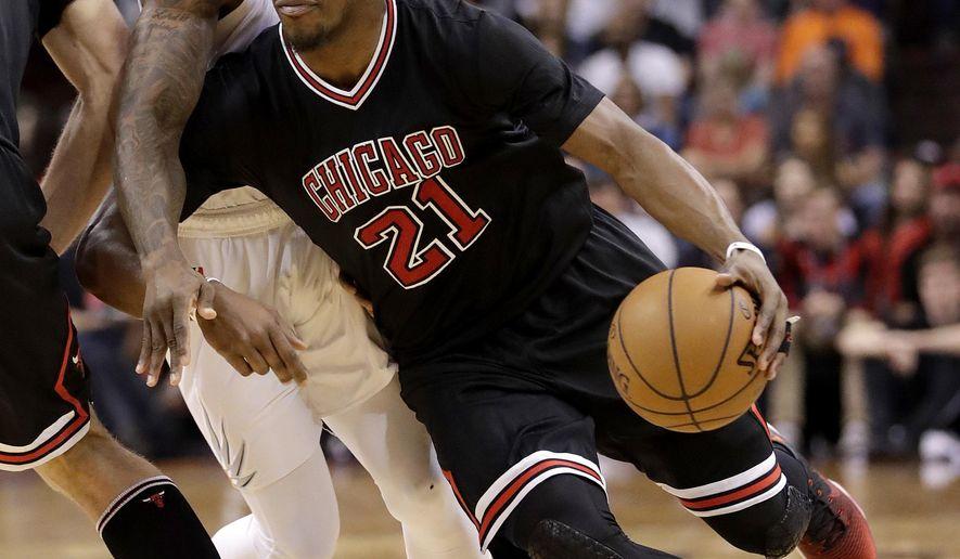 Chicago Bulls forward Jimmy Butler (21) drives around Phoenix Suns guard Eric Bledsoe during the first half of an NBA basketball game, Friday, Feb. 10, 2017, in Phoenix. (AP Photo/Matt York)