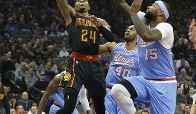 Atlanta Hawks forward Kent Bazemore, left, goes to the basket against Sacramento Kings' Arron Afflalo, center, and DeMarcus Cousins during the first quarter of an NBA basketball game Friday, Feb. 10, 2017, in Sacramento, Calif. (AP Photo/Rich Pedroncelli)