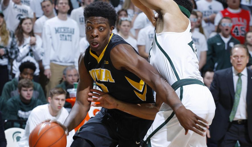 Iowa's Tyler Cook, left, drives against Michigan State's Kenny Goins during the first half of an NCAA college basketball game, Saturday, Feb. 11, 2017, in East Lansing, Mich. (AP Photo/Al Goldis)