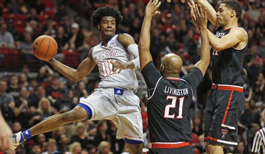 Kansas' Josh Jackson (11) passes the ball around Texas Tech's Anthony Livingston (21) and Zach Smith (11) during an NCAA basketball game Saturday, Feb. 11, 2017, in Lubbock, Texas. (AP Photo/Brad Tollefson)