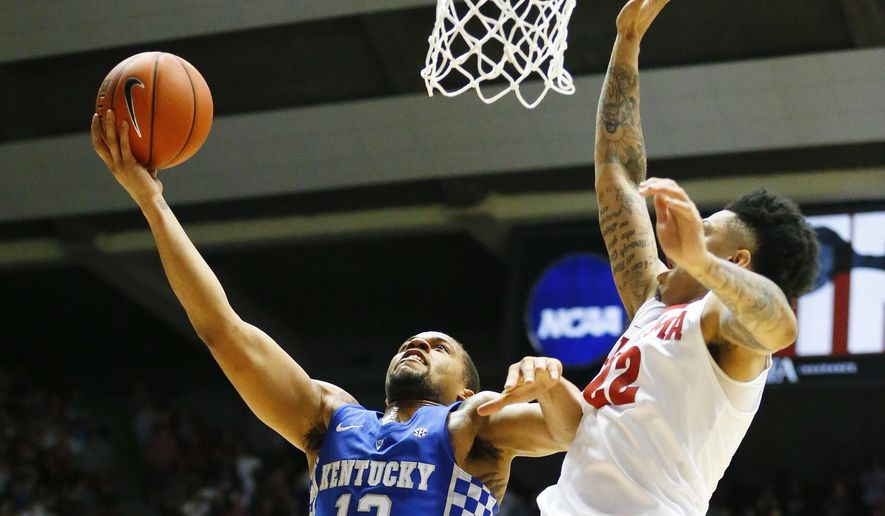 Kentucky guard Isaiah Briscoe, left, shoots and scores against Alabama guard Ar'Mond Davis during the first half of an NCAA college basketball game, Saturday, Feb. 11, 2017, in Tuscaloosa, Ala. (AP Photo/Brynn Anderson)