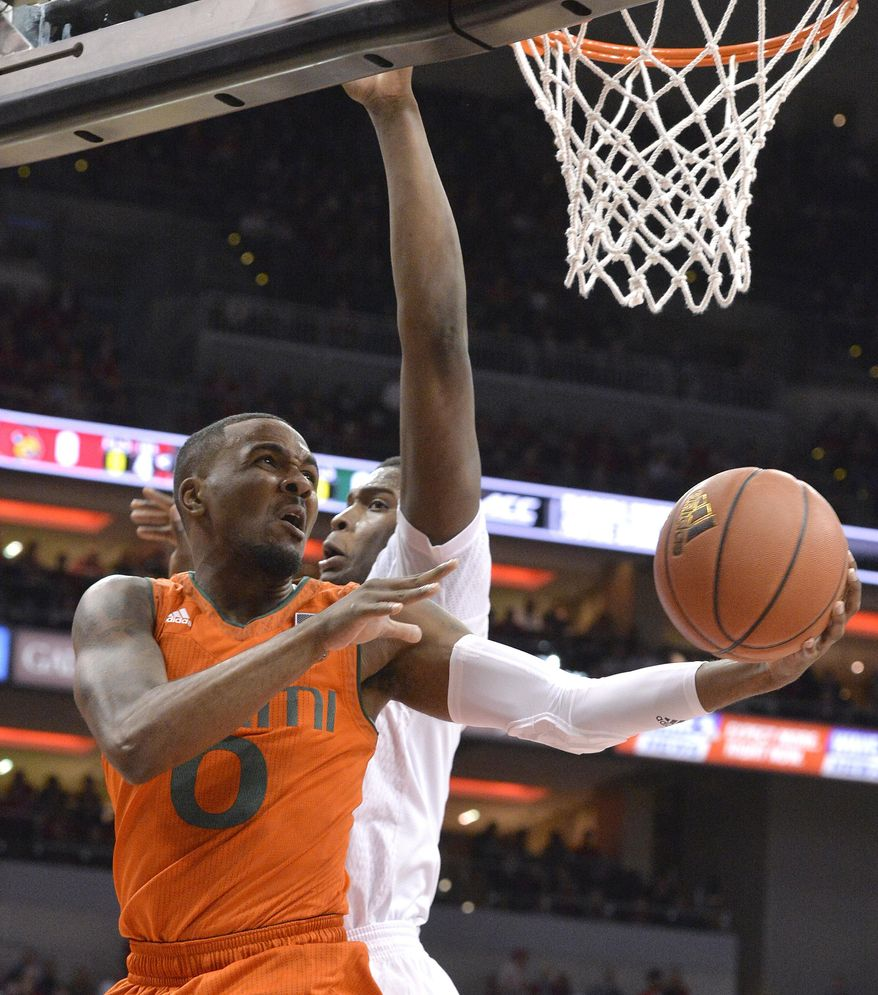 Miami's Ja'Quan Newton (0) goes in for a layup around the defense of Louisville's Jaylen Johnson (10) during the first half of an NCAA college basketball game, Saturday, Feb. 11, 2017, in Louisville, Ky. (AP Photo/Timothy D. Easley)