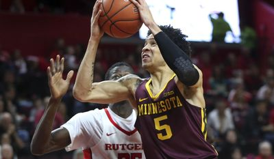 Minnesota guard Amir Coffey (5) looks to take a shot past Rutgers forward Issa Thiam, (35) of Senegal, during the first half of an NCAA college basketball game, Saturday, Feb. 11, 2017, in Piscataway, N.J. (AP Photo/Mel Evans)
