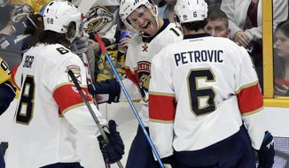 Florida Panthers left wing Jonathan Huberdeau (11) celebrates with Jaromir Jagr (68), of the Czech Republic, and Alex Petrovic (6) after Huberdeau scored a goal against the Nashville Predators during the third period of an NHL hockey game Saturday, Feb. 11, 2017, in Nashville, Tenn. (AP Photo/Mark Humphrey)