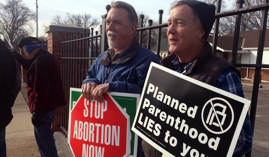 Marvin Naegele, 62, of Walnut, Iowa, left,  and Lon Schroeder, 61, of Council Bluffs hold protest signs during a protest on Saturday, Feb. 11, 2017, in Council Bluffs, Iowa. Rallies aimed at urging Congress and President Donald Trump to end federal funding for Planned Parenthood are scheduled across the country. (AP Photo/Margery Beck) **FILE**