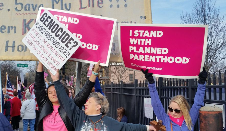 A Planned Parenthood supporter and opponent try to block each other's signs during a protest and counter-protest Saturday, Feb. 11, 2017 in St. Louis. Rallies aimed at urging Congress and President Donald Trump to end federal funding for Planned Parenthood are scheduled across the country. (AP Photo/Jim Salter)