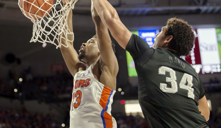 Florida forward Kevarrius Hayes (13) dunks the ball over Texas A&M center Tyler Davis (34) during the first half of an NCAA college basketball game in Gainesville, Fla., Saturday, Feb. 11, 2017. (AP Photo/Ron Irby)
