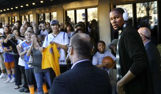 Golden State Warriors' Kevin Durant, right, walks toward cheering fans where he greeted several and signed a few autographs as he left a downtown Oklahoma City hotel with teammates to board a bus for a ride to the Warriors' NBA basketball game against his former team, the Oklahoma City Thunder, Saturday, Feb. 11, 2017. (Jim Beckel/The Oklahoman via AP)