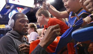 Golden State Warriors forward Kevin Durant signs autographs for fans in Oklahoma City before playing against his former team on Saturday. (Associated Press)
