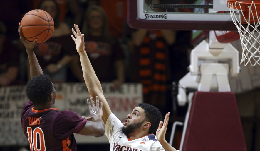 Justin Bibbs (10) of Virginia Tech scores over Darius Thompson (51) of Virginia in the first half of an NCAA college basketball game in Blacksburg, Va., Sunday, Feb. 12, 2017. (Matt Gentry/The Roanoke Times via AP)