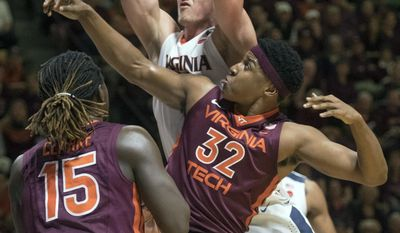 Virginia center Jack Salt, top, grabs a rebound against Virginia Tech forward Zach LeDay (32) in the first half of an NCAA college basketball game Sunday, Feb. 12, 2017, in Blacksburg, Va. (AP Photo/Don Petersen)