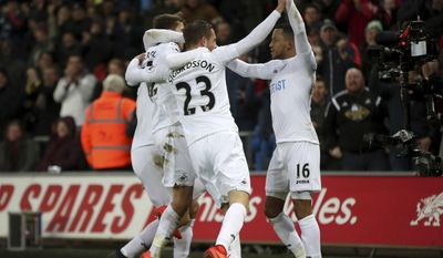 Swansea City's Martin Olsson, right, celebrates scoring his side's second goal of the game during the English Premier League match Swansea against Leicester at the Liberty Stadium, Swansea, Wales, Sunday Feb. 12, 2017. (Nick Potts/PA via AP)