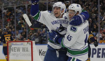 Vancouver Canucks Alexandre Burrows (14) and Michael Chaput (45) celebrate a goal during the second period of an NHL hockey game against the Buffalo Sabres, Sunday, Feb. 12, 2017, in Buffalo, N.Y. (AP Photo/Jeffrey T. Barnes)
