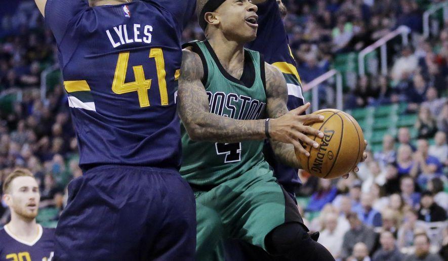 Boston Celtics guard Isaiah Thomas, right, goes to the basket as Utah Jazz forward Trey Lyles (41) defends during the second half of an NBA basketball game Saturday, Feb. 11, 2017, in Salt Lake City. The Celtics won 112-104. (AP Photo/Rick Bowmer)