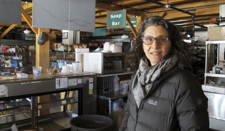 In this Monday Feb. 6, 2017 photo, Lyssa Papazian, of the Putney Historical Society, stands inside the closed Putney General Store, in Putney, Vt. Originally built in the late 1700s, the store was heavily damaged by fire in 2008 and, as repairs were nearing completion a year later, was destroyed by an arson fire. It was rebuilt again and reopened in 2011. Now the general store and pharmacy is closed again due to the death of its pharmacist. The historical society, which owns the building, hopes to find someone to run a new store in the structure. (AP Photo/Wilson Ring)