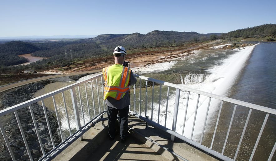 Jason Newton, of the Department of Water Resources, takes a picture of water going over the emergency spillway at Oroville Dam Saturday, Feb. 11, 2017, in Oroville, Calif. Water started flowing over the emergency spillway, at the nation's tallest dam, for the first time Saturday morning after erosion damaged the Northern California dam's main spillway.(AP Photo/Rich Pedroncelli)