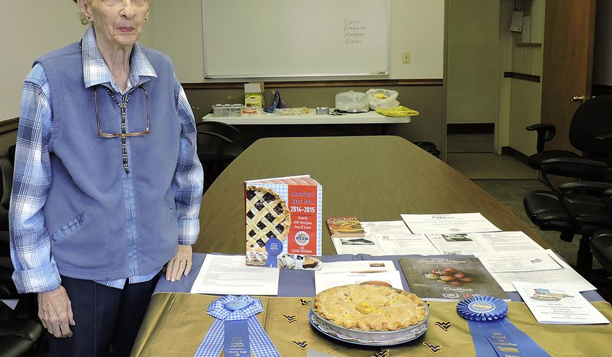 In this undated photo, Carolyn Blakemore stands next to a display that presents her awards for best apple pie in Fairmont, W.Va. There is nothing more American than apple pie, and Blakemore has been known to make the best apple pie for years. (Sarah Goodrich/Times West Virginian, via AP)
