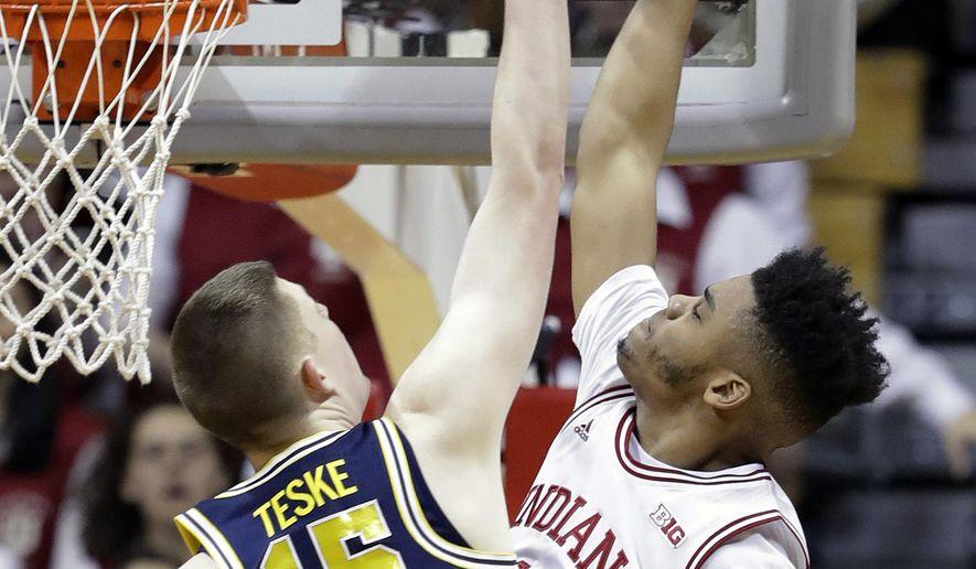 Indiana's Juwan Morgan, right, dunks against Michigan's Jon Teske during the first half of an NCAA college basketball game Sunday, Feb. 12, 2017, in Bloomington, Ind. (AP Photo/Darron Cummings)