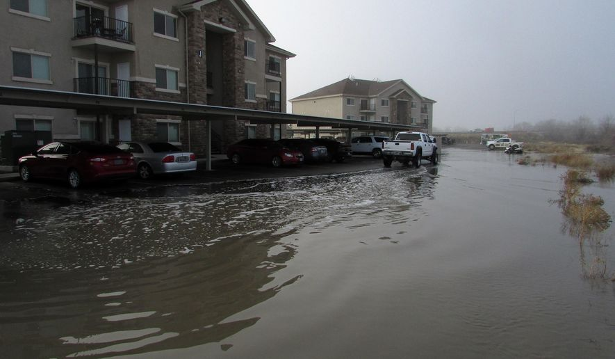 Water from the Humboldt River flows into a parking lot behind apartment buildings off 12th Street in Elko, Nev., on Saturday morning, Feb. 11, 2017. (Jeff Mullins/The Daily Free Press via AP)