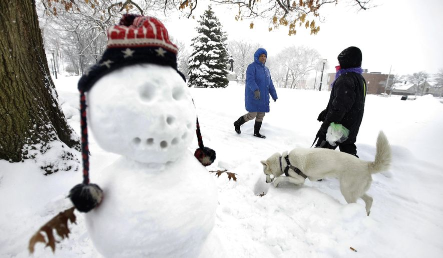 Tina Fuller, 60, of Waltham, Mass., behind center, walks past a snowman and a person walking a dog, Sunday, Feb. 12, 2017, in Waltham, Mass. (AP Photo/Steven Senne) ** FILE **