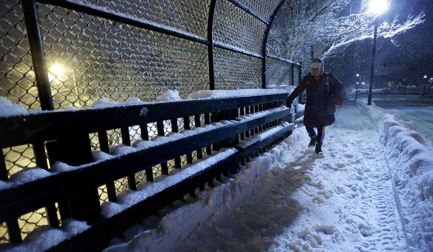 A person walks on a snow-covered sidewalk on a bridge near a commuter rail station Sunday, Feb. 12, 2017, in Wellesley, Mass. Another winter blast of snow and strong winds moved into the Northeast on Sunday to the delight of some and the consternation of others, just days after the biggest storm of the season dumped up to 19 inches of snow in the region. (AP Photo/Steven Senne)