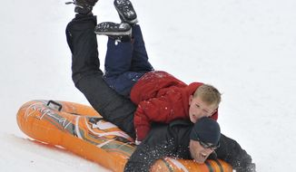 Brian Wilson, of North Attleboro, Mass., and his son Adam, 8, hit a jump on the way down a hill in the rear of the WWI Memorial Park in North Attleboro, Sunday, Feb. 12, 2017. Another several inches of snow is expected into Monday. (Mark Stockwell/The Sun Chronicle via AP)