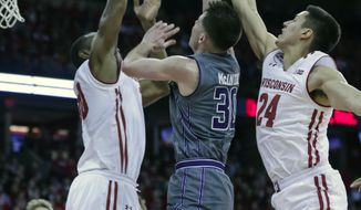 Indiana's Bryant McIntosh (30) shoots between Wisconsin's Vitto Brown, left, and Bronson Koenig during the first half of an NCAA college basketball game, Sunday, Feb. 12, 2017, in Madison, Wis. (AP Photo/Andy Manis)