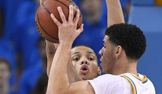 UCLA guard Lonzo Ball, right, tries to pass the ball as Oregon State forward Ben Kone defends during the first half of an NCAA college basketball game, Sunday, Feb. 12, 2017, in Los Angeles. (AP Photo/Mark J. Terrill)