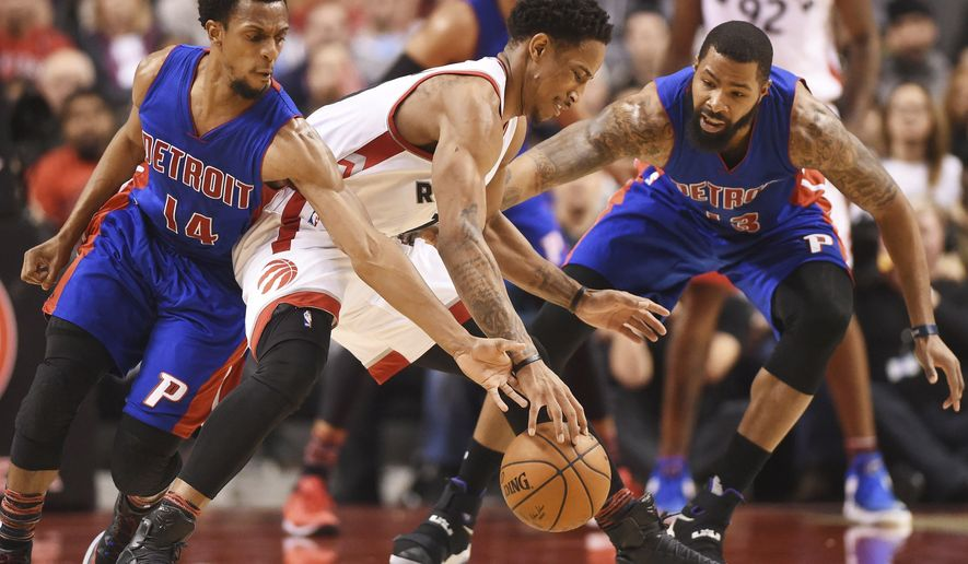 Toronto Raptors guard DeMar DeRozan (10) tries to protect the ball from Detroit Pistons guard Ish Smith (14) and forward Marcus Morris (13) during second-half NBA basketball game action in Toronto, Sunday, Feb. 12, 2017.(Frank Gunn/The Canadian Press via AP)