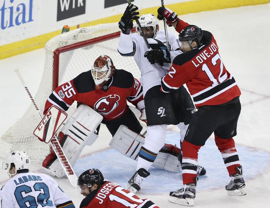 New Jersey Devils goalie Cory Schneider (35) watches for the puck as San Jose Sharks forward Joel Ward (42) and New Jersey Devils defenseman Ben Lovejoy (12) battle for position during the first period of an NHL hockey game, Sunday, Feb. 12, 2017, in Newark, N.J. (AP Photo/Mel Evans)