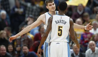 Denver Nuggets forward Juancho Hernangomez, back, is congratulated by guard Will Barton after hitting a shot against the Golden State Warriors in the second half of an NBA basketball game Monday, Feb. 13, 201, in Denver. The Nuggets won 132-110. (AP Photo/David Zalubowski)