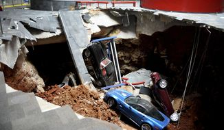 FILE - In this Feb. 12, 2014, file photo, cars lie in a sinkhole that opened up at the Skydome showroom in the National Corvette Museum in Bowling Green, Ky. The museum said a prized Corvette still covered in dirt and debris from its 2014 fall into the sinkhole has been moved from display to undergo repairs. The museum said the restoration work on the 1962 Corvette will be done at the museum and visitors will be able to watch the progress in restoring the car. (AP Photo/Michael Noble Jr., File)