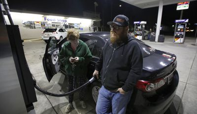 Chris Mitchell fills his car with gas as his daughter, Austin, checks her mobile phone before evacuating Oroville, Calif., Sunday, Feb. 12, 2017. Mitchell was among the thousands of area residents who left their homes Sunday evening as officials ordered residents near the Oroville Dam in Northern California to evacuate the area after an emergency spillway of the dam severely eroded. (AP Photo/Rich Pedroncelli)