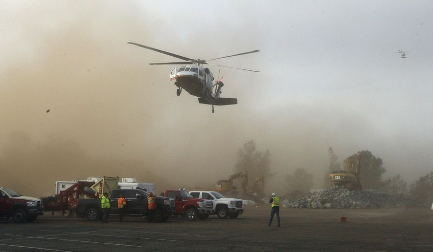 A helicopter kicks up dust as it lands at a staging area near the Oroville Dam on Monday, Feb. 13, 2017, in Oroville, Calif. State officials have discussed using helicopters to drop loads of rock on the damaged emergency spillway of the dam. (AP Photo/Rich Pedroncelli)