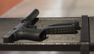 A handgun with a silencer and two magazines are shown at a gun range in Atlanta. (Associated Press) ** FILE **