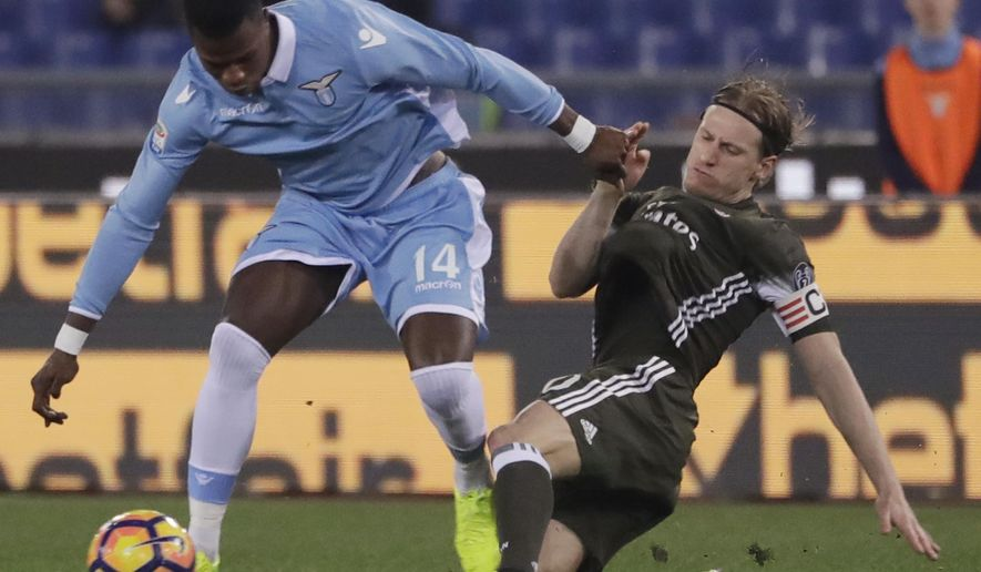 Lazio's Keita, left, and AC Milan's Ignazio Abate vie for the ball during an Italian Serie A soccer match between Lazio and Milan, at the Olympic stadium in Rome, Monday, Feb. 13, 2017. (AP Photo/Gregorio Borgia)