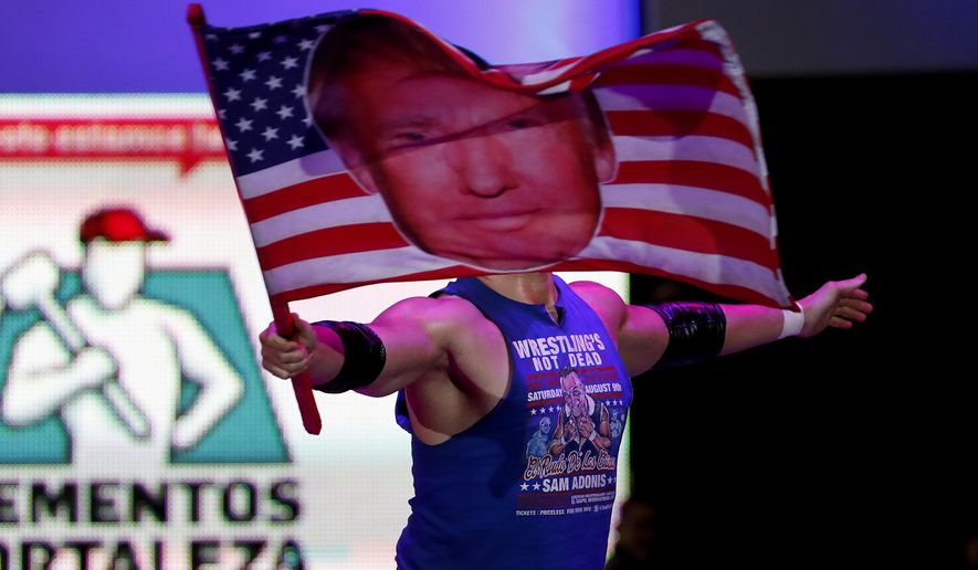 Wrestler Sam Polinsky aka Sam Adonis takes the ring at Arena Mexico waving an American flag emblazoned with a photo of U.S. President Donald Trump, in Mexico City, Sunday, Feb. 12, 2017. He's the guy Mexicans love to hate: The American pro wrestler has become a sensation in Mexico City by adopting the ring persona of a flamboyant Trump supporter. (AP Photo/Eduardo Verdugo)