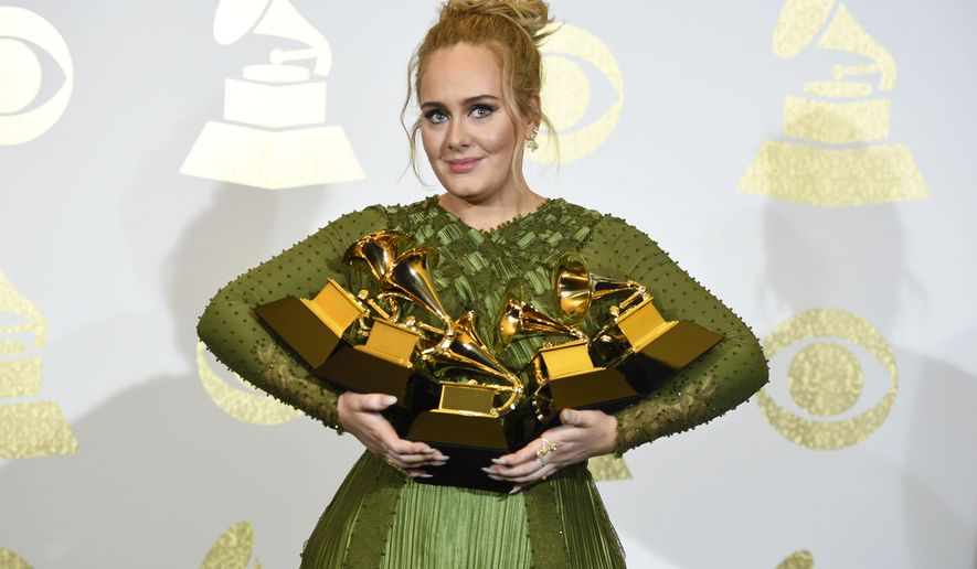 "Adele poses in the press room with the awards for album of the year for ""25"", song of the year for ""Hello"", record of the year for ""Hello"", best pop solo performance for ""Hello"", and best pop vocal album for ""25"" at the 59th annual Grammy Awards at the Staples Center on Sunday, Feb. 12, 2017, in Los Angeles. (Photo by Chris Pizzello/Invision/AP)"
