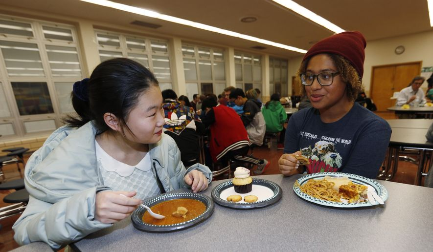 In this Jan. 27, 2017 photo, foreign exchange student Miaofan Chen, left, of Hefei, China, chats with Thandi Glick during a potluck meal for Chinese exchange students and their families at a school in Denver. Hosting foreign students is a way to connect with the world as well as see our country through another's eyes. (AP Photo/David Zalubowski)