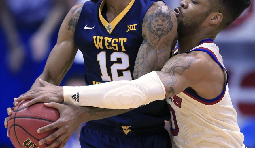 Kansas guard Frank Mason III (0) reaches around West Virginia guard Tarik Phillip (12) during the first half of an NCAA college basketball game in Lawrence, Kan., Monday, Feb. 13, 2017. (AP Photo/Orlin Wagner)