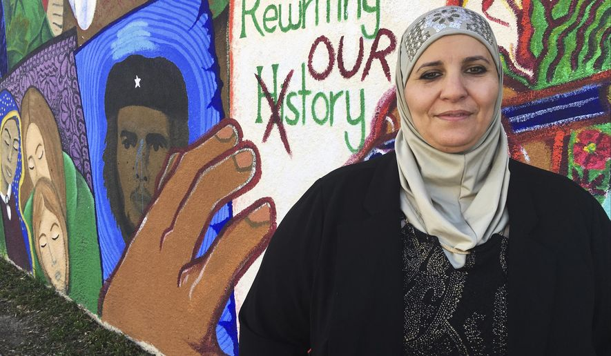 In this Wednesday, Feb, 1, 2017 photo, activist Samia Assed stands in front of a mural at the Albuquerque Center for Peace and Justice coalition in Albuquerque, N.M. Assed, a Palestinian-American, has now turned her fears over Donald Trump's election into action, joining what advocacy groups said are hundreds, possibly thousands of women of color, who are exploring making a run for public office. (AP Photo/Russell Contreras)