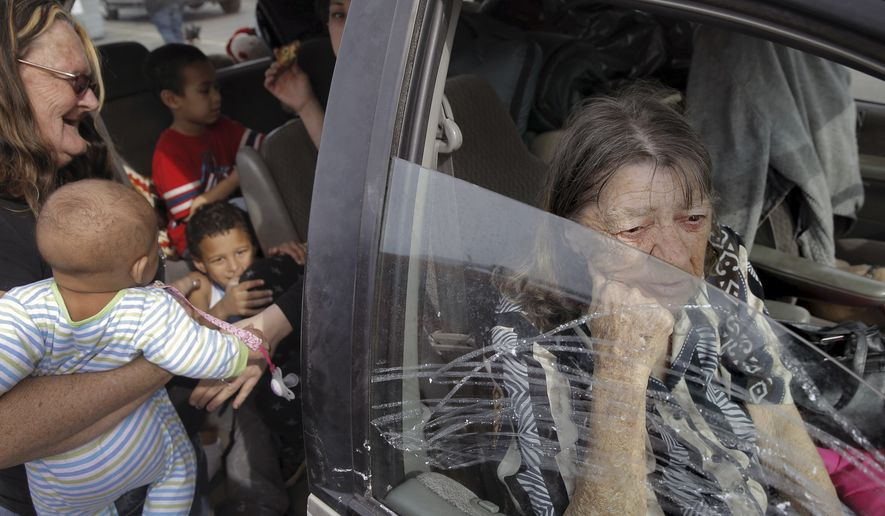 In this photo taken Monday, Feb. 13, 2017, Gerldeen Trammell, right, sits in her family's car with her daughter and grandchildren from Oroville at the evacuation center at Silver Dollar Fairgrounds in Chico, Calif. Authorities on Tuesday lifted an evacuation order Tuesday for thousands of California residents who live below the nation's tallest dam after declaring that the risk of catastrophic collapse of a damaged spillway had been significantly reduced. (Carlos Avila Gonzalez/San Francisco Chronicle via AP)