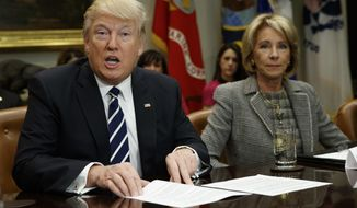 Education Secretary Betsy DeVos listens at right as President Donald Trump speaks during a meeting with parents and teachers, Tuesday, Feb. 14, 2017, in the Roosevelt Room of the White House in Washington. (AP Photo/Evan Vucci)