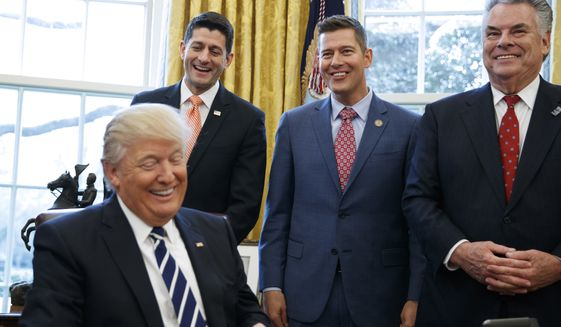 President Donald Trump, jokes with, from left, House Speaker Paul Ryan of Wis., Rep. Sean Duffy, R-Wis., and Rep. Peter King, R-N.Y. in the Oval Office of the White House in Washington, Tuesday, Feb. 14, 2017, after the president signed House Joint Resolution 41.   (AP Photo/Evan Vucci)