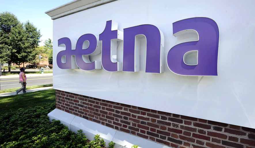 FILE - In this Tuesday, Aug. 19, 2014, file photo, a pedestrian walks past a sign for Aetna Inc., at the company headquarters in Hartford, Conn. Aetna and Humana are calling off a $34 billion deal to combine the two major health insurers after a federal judge, citing antitrust concerns, shot down the deal. (AP Photo/Jessica Hill, File)