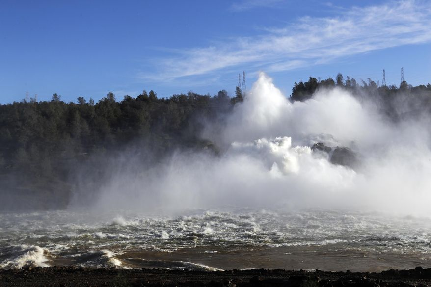 Water gushes from the Oroville Dam's main spillway Tuesday, Feb. 14, 2017, in Oroville, Calif. Crews working around the clock atop the crippled Oroville Dam have made progress repairing the damaged spillway, state officials said Tuesday. (AP Photo/Marcio Jose Sanchez)